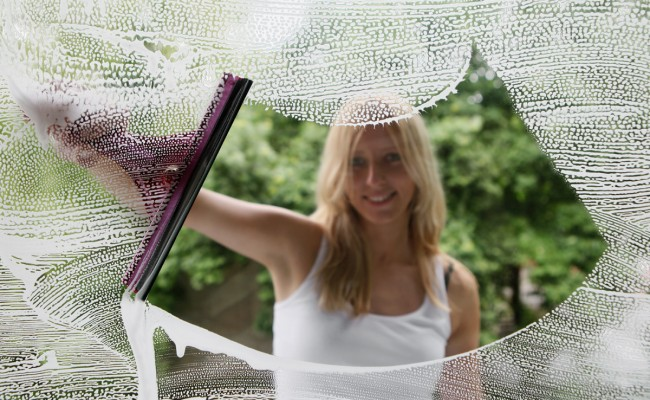 Woman cleaning the window, focus on a glass
